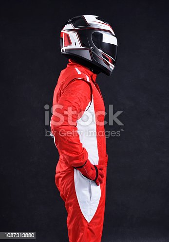Race car driver on a black background, side view
