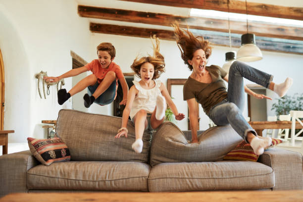 race for the best spot on the sofa. mother and children jumping. - divano foto e immagini stock