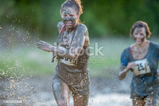 Two women are running through a mud pit. They are covered in mud. There are race numbers on their shirts.