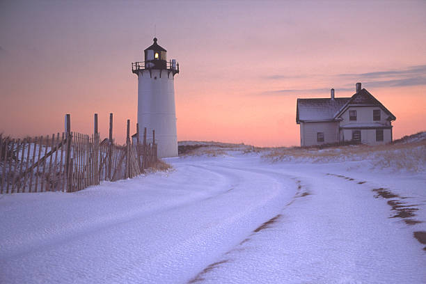 Race Point Lighthouse and House with Snowy Landscape at Sunset  provincetown stock pictures, royalty-free photos & images