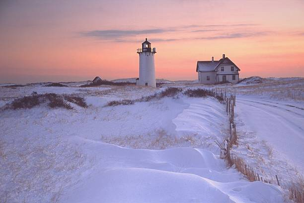 Race Point Lighthouse Cape Cod Race Point Lighthouse is located on Cape Cod where it guards the entrance to Provincetown Harbor. Surrounded by wild windswept dunes, it is accessible only by four-wheel-drive vehicle or by foot. Photo taken at sunset surrounded by snow covered dunes. Cape Cod is famous, worldwide, as a coastal vacation destination  provincetown stock pictures, royalty-free photos & images