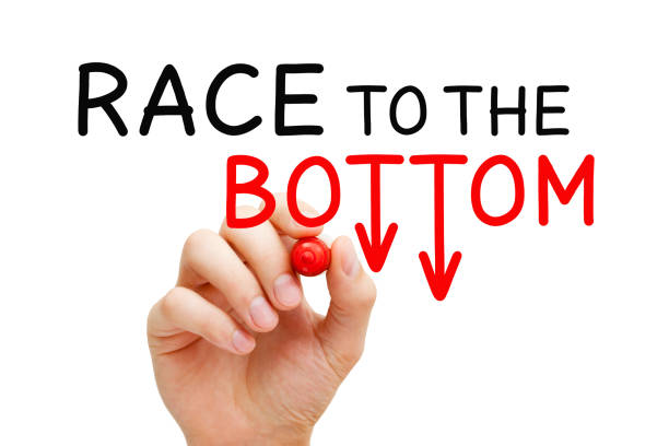 Race To The Bottom Price War Concept Hand writing Race to the Bottom or Price War concept with marker on transparent wipe board isolated on white. at the bottom of stock pictures, royalty-free photos & images