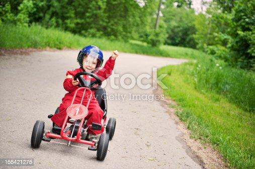 Little boy winning a go-kart race.