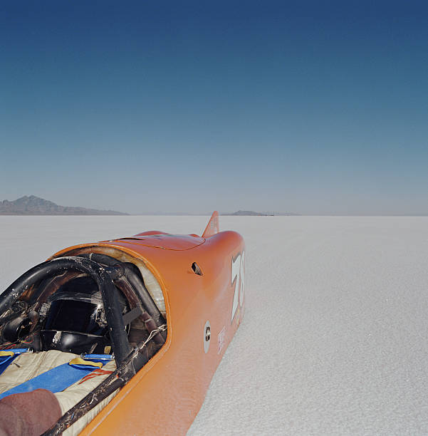 Racecar driver lying in streamliner car, elevated view Racecar driver lying in streamliner car, elevated view bonneville salt flats stock pictures, royalty-free photos & images