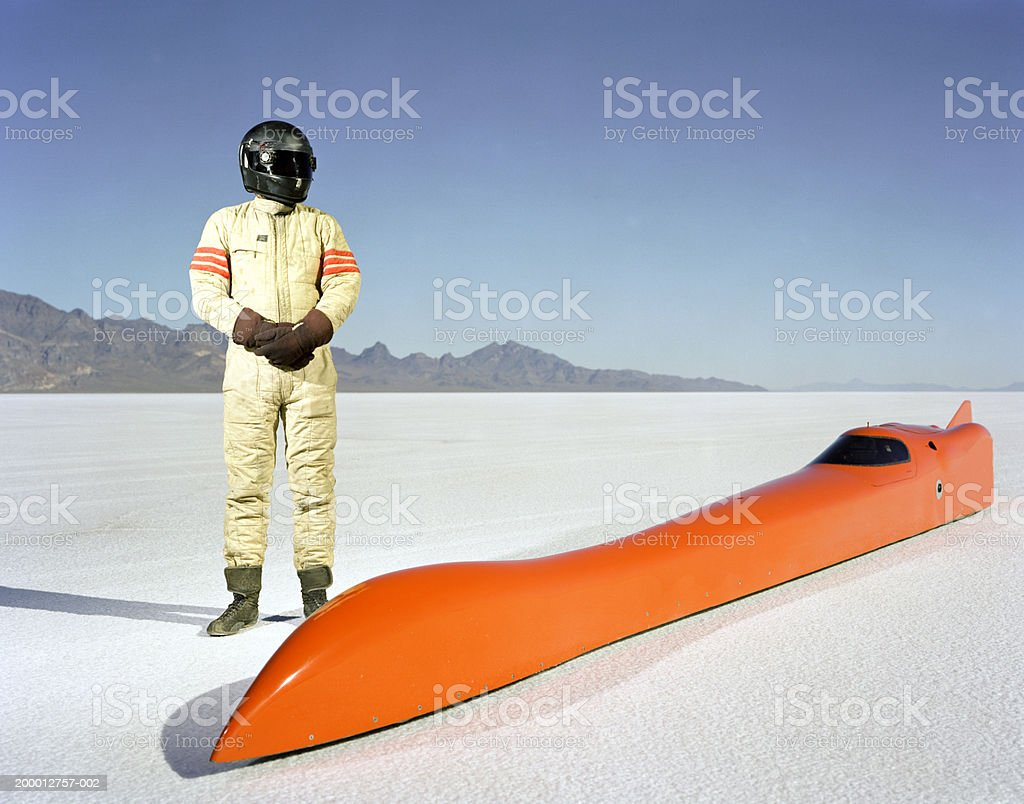 Racecar driver standing alongside streamliner car on raceway Bonneville Salt Flats, Utah, USA 60-69 Years Stock Photo
