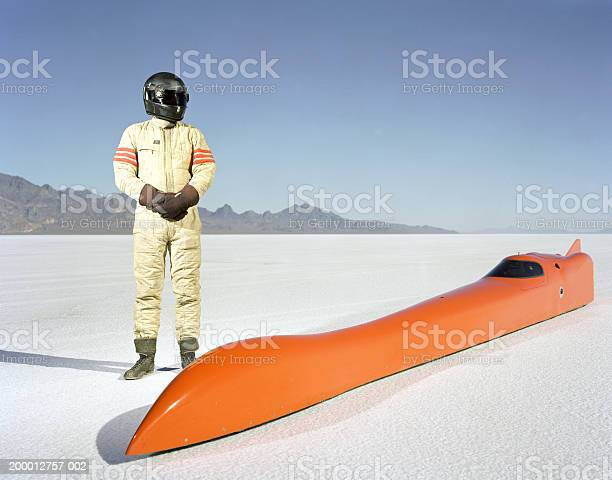 Racecar Driver Standing Alongside Streamliner Car On Raceway Stock Photo - Download Image Now