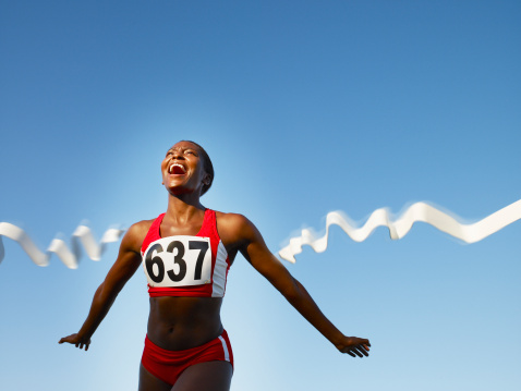 istock Racer crossing the finish line smiling 77930912