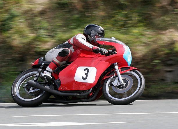 a racer on a red motorcycle with matching gear on the road - motorbike racing stock photos and pictures