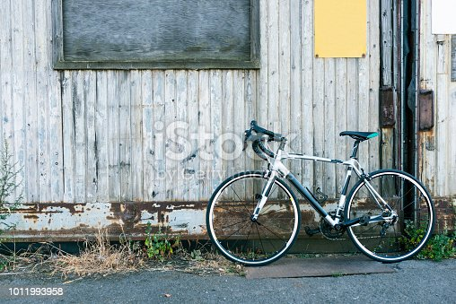 istock Racing bicycle standing next to big old door made of wood 1011993958
