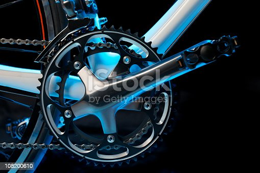 Pedal, crank, front sprockets and derailleur shot in cool light in the studio. The bike is a brand-new top model worth thousands of dollars.
