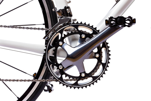 Pedal, crank, front sprockets and derailleur shot on a white background in the studio. The bike is a brand-new top model worth thousands of dollars. Camera: Canon EOS 1Ds Mark III.