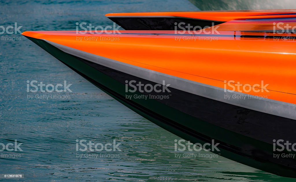 Racing boat, orange and black bow on water stock photo