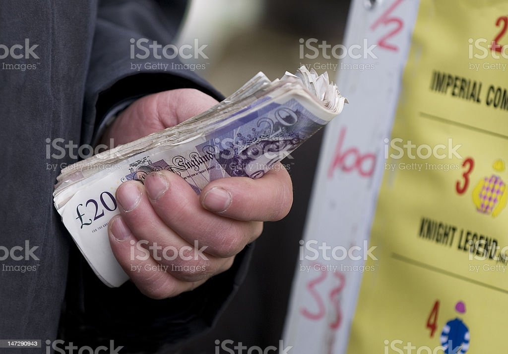 Racing Bookie collecting money on bets for horses stock photo