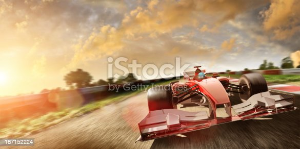 Image of racing car with intentional motion blur driving fast on racetrack at sunset
