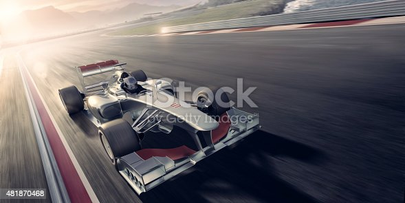 A mid action image of a generic formula one racing car driven by a professional racing driver during an auto sports event during a race. The action takes place on a generic race track near mountains and the sea at evening under a bright sunset. With motion blur on the racetrack. With copyspace.