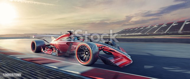 A close up wide angle image of a generic red, white and black racing car moving at high speed on the outer edge of the track just coming out of a corner. The car is racing at a generic location, with empty stands in the distance, at sunset or dawn.