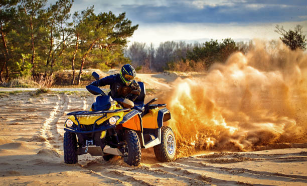 Racing in the sand on a four-wheel drive quad. Racing powerful quad bike on the difficult sand in the summer. quadbike stock pictures, royalty-free photos & images