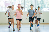 A multi-ethnic group of children are indoors in a health center. They are wearing casual clothing and running shoes. They are running towards the camera.