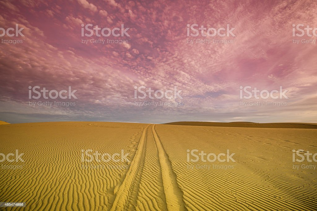 Racing quad jumping sand dunes stock photo