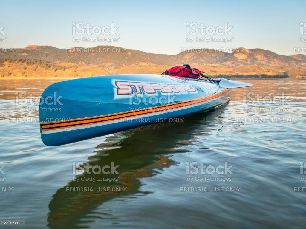 Racing stand up paddleboard on lake stock photo