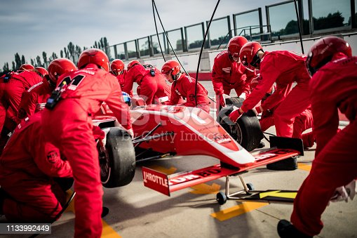 Pit crew in red uniforms changing tires on formula race car during pit stop.