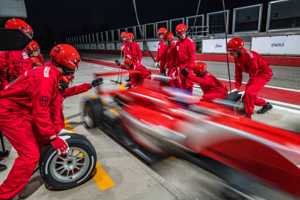 Racing team working at pit stop Pit crew in red uniforms changing tires on formula race car during pit stop. speed stock pictures, royalty-free photos & images