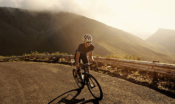 Racing towards her fitness goal Shot of a cyclist riding on a mountain roadhttp://195.154.178.81/DATA/i_collage/pu/shoots/804604.jpg individual event stock pictures, royalty-free photos & images