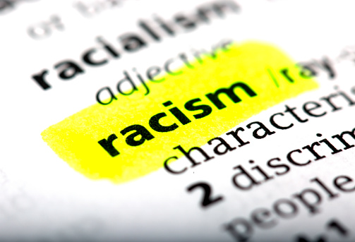 Racism is a word printed and highlighted in the English dictionary