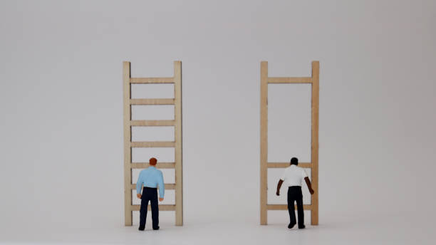 Racist concepts in employment and promotion. Miniature people and miniature wooden ladders. Racist concepts in employment and promotion. Miniature people and miniature wooden ladders. unbalanced stock pictures, royalty-free photos & images