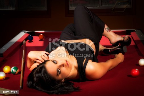Beautiful model reclined on a red felt pool table