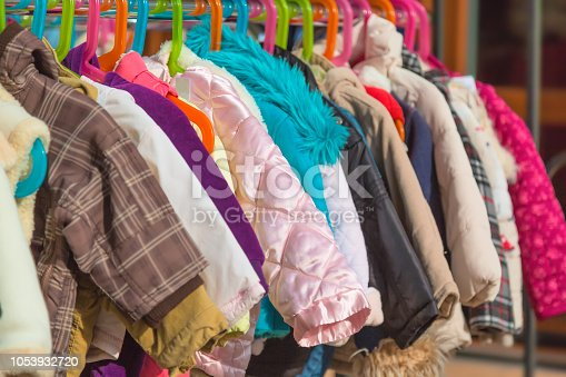 Rack of baby and children used dress, clothes displayed at outdoor hanger market for sale