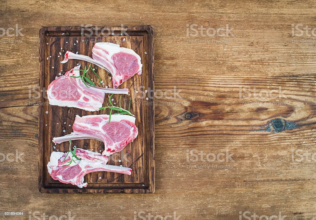 Rack of Lamb with rosemary and spices on rustic chopping stock photo
