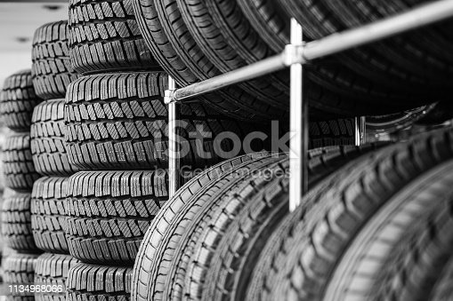 Rack with variety of new car tires in automobile store, selective focus