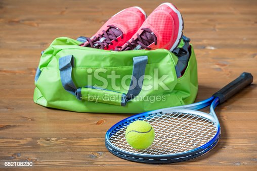 istock Racket and ball for tennis in focus on the background of bag with sneakers on the floor 682108230