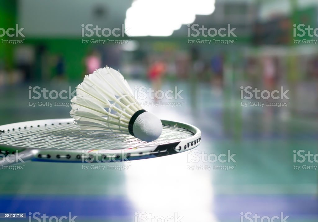 racket and white shuttlecock over blurred of badminton court with players playing badminton foto stock royalty-free