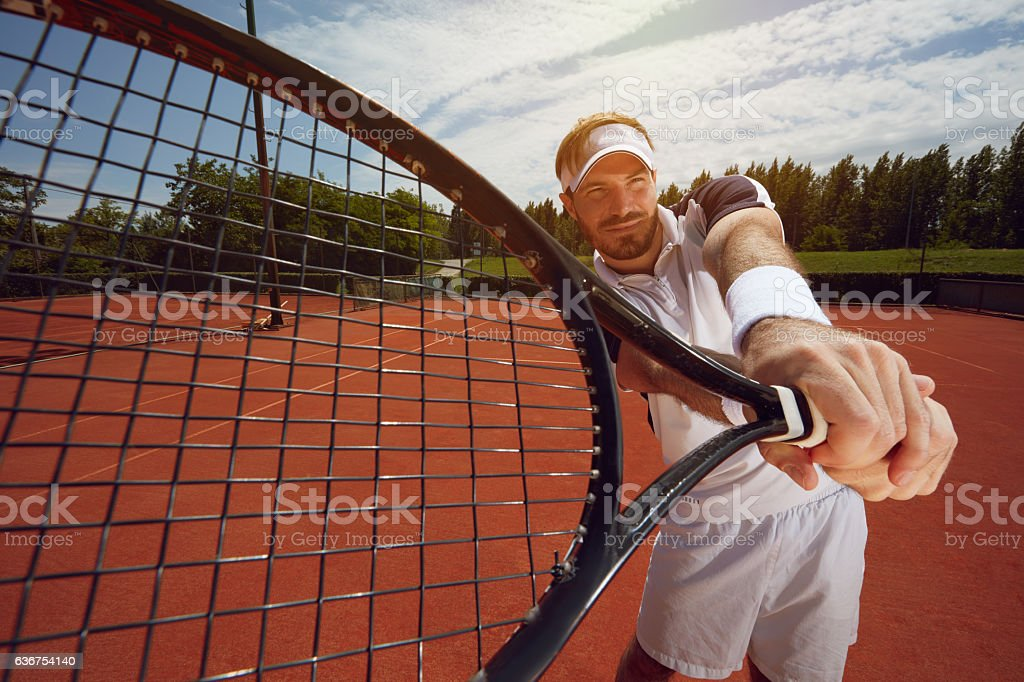 Racket in tennis player's hand stock photo