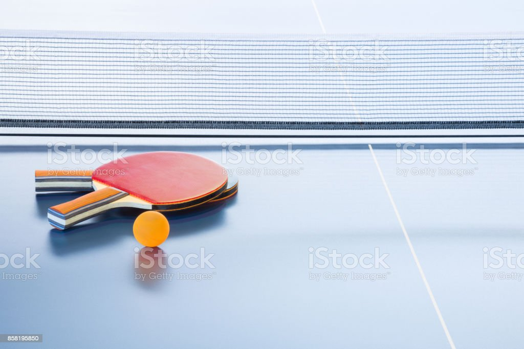 Rackets and ball on the blue tennis table. Indoor sport activity....