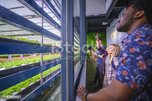 Visitors to a floor to ceiling indoor farm facility experiencing firsthand the potential for a sustainable future.