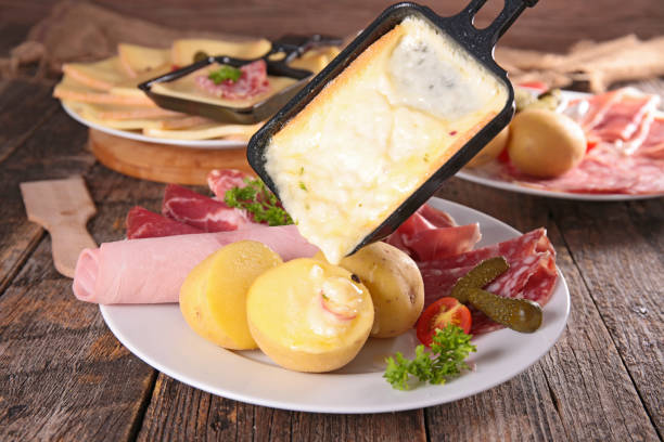 fromage à raclette fondu sur pommes de terre - raclette photos et images de collection