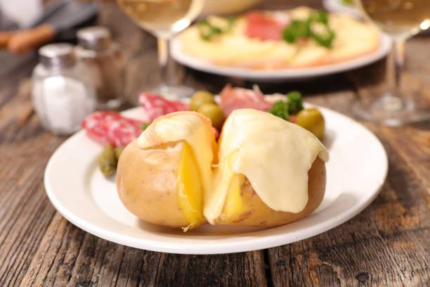 fromage à raclette fondant sur pomme de terre - raclette photos et images de collection