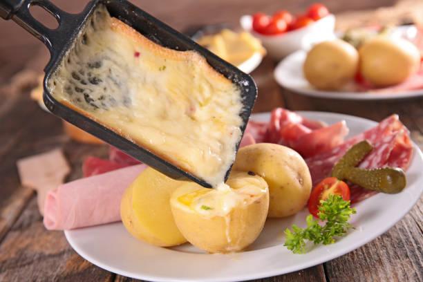 fromage raclette fondant avec pommes de terre, salami et jambon - raclette photos et images de collection