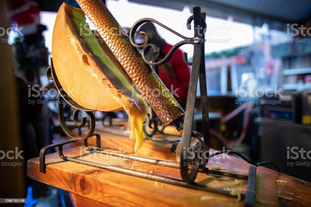 Raclette (traditionelle geschmolzene Käsegericht) für Verkauf stand auf Weihnachtsmarkt in Paris - Lizenzfrei Abnehmen Stock-Foto