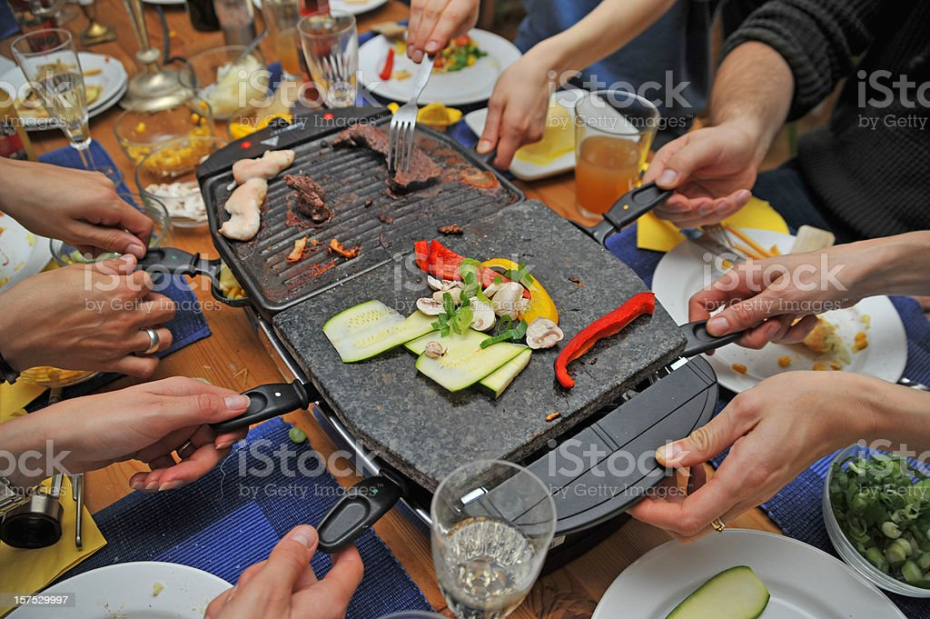 raclette with many hands stock photo
