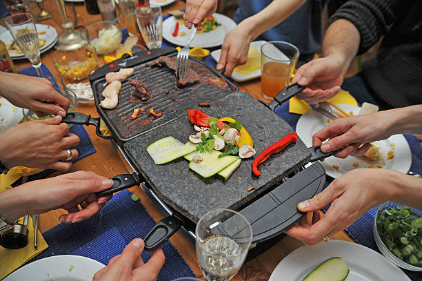 raclette avec beaucoup de mains - raclette photos et images de collection