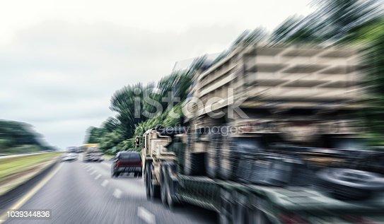 istock Radial Blur US Military Semi-Truck Flatbed Hauling Dump Truck 1039344836