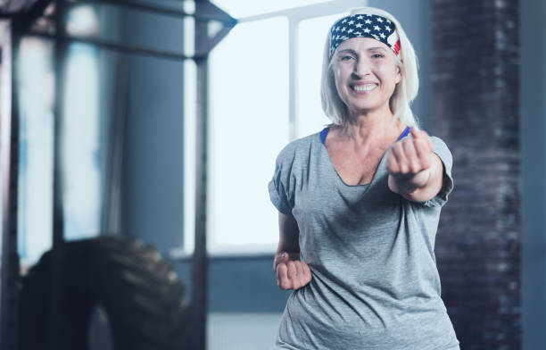 radiant woman looking into camera while taking exercise class - runner rehab gym foto e immagini stock