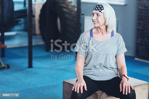 936573360 istock photo Radiant woman sitting on box while resting in gym 936572732