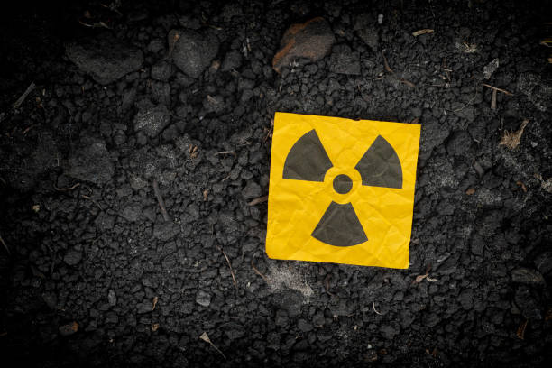 Radiation warning sign on soil background Radiation warning sign on soil background. Close up. radioactive contamination stock pictures, royalty-free photos & images