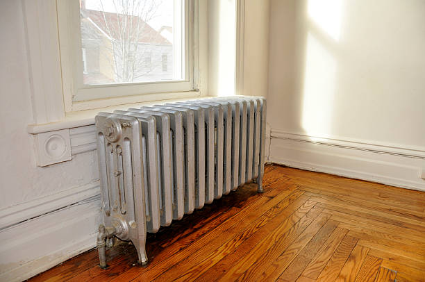 A radiator in a old home next to a window stock photo