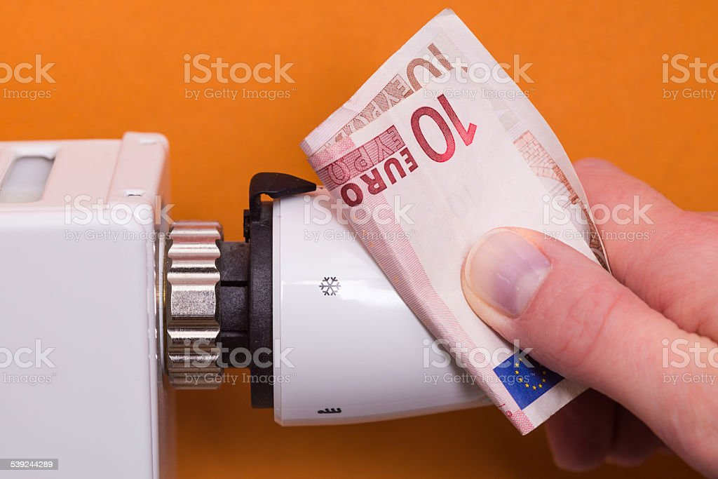 Radiator thermostat, banknote and hand - brown stock photo